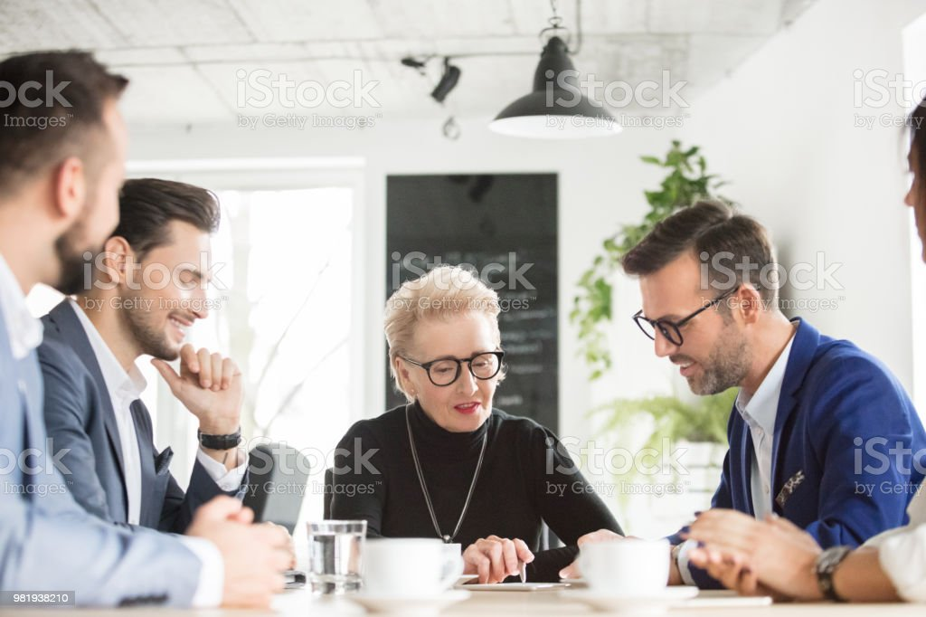 Senior businesswoman meeting with team Senior businesswoman discussing new business plan with team. Senior executive explaining strategy with coworkers, all looking at digital tablet on table. Active Seniors Stock Photo