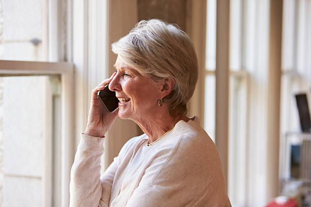 senior femme d'affaires sur téléphone portable dans le bureau - seulement des femmes seniors photos et images de collection