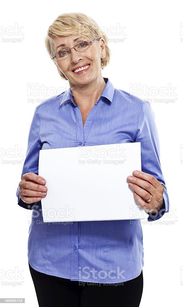 Senior businesswoman Portrait of smiling senior businesswoman holding a white piece of paper. Studio shot, white background. 60-69 Years Stock Photo