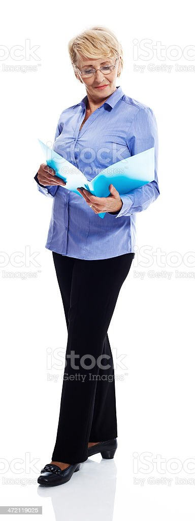 Senior businesswoman Full lenght portrait of confident senior businesswoman reading documents. Studio shot, white background. 60-69 Years Stock Photo