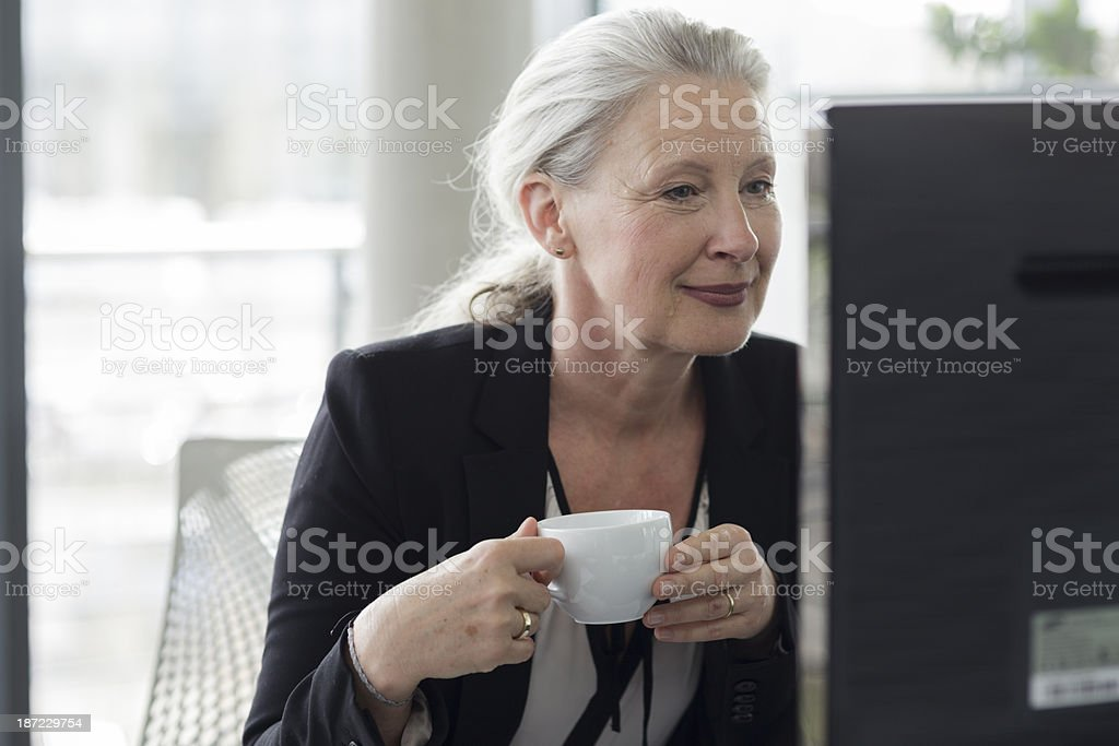 Senior Businesswoman Reading at Computer while Drinking Coffee royalty-free stock photo