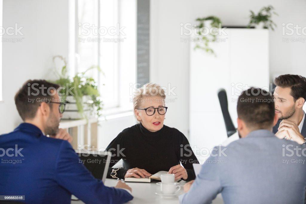 Senior businesswoman sharing ideas in meeting Senior businesswoman sharing her views with colleagues in meeting. Business team brainstorming over business ideas in meeting. Active Seniors Stock Photo