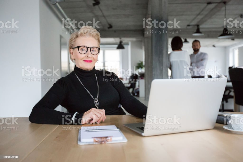 Senior businesswoman sitting at her desk Portrait of beautiful senior businesswoman sitting at her desk with laptop and colleagues standing in background Active Seniors Stock Photo