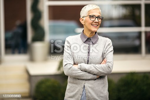 Short hair senior business woman standing outdoor and smiling