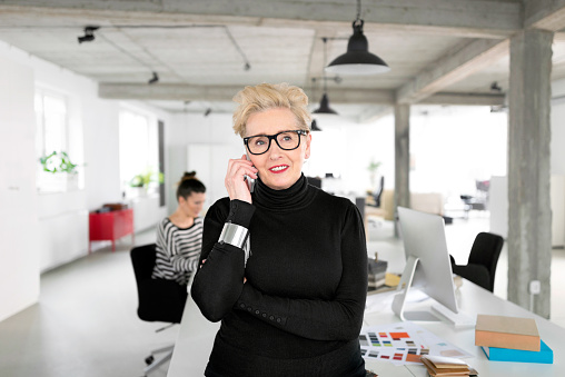 Senior Businesswoman Talking On Mobile Phone In The Studio Stock Photo - Download Image Now