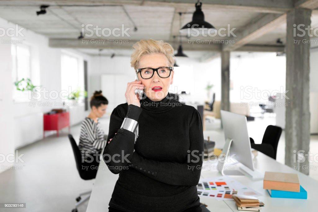 Senior businesswoman talking on phone in the office Portrait of senior elegant businesswoman talking on phone in her office. 60-69 Years Stock Photo