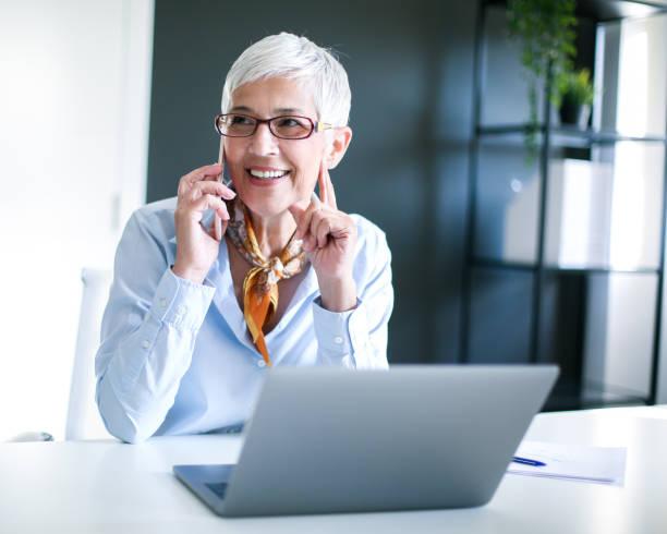 Senior businesswoman talking on smartphone in modern office. stock photo