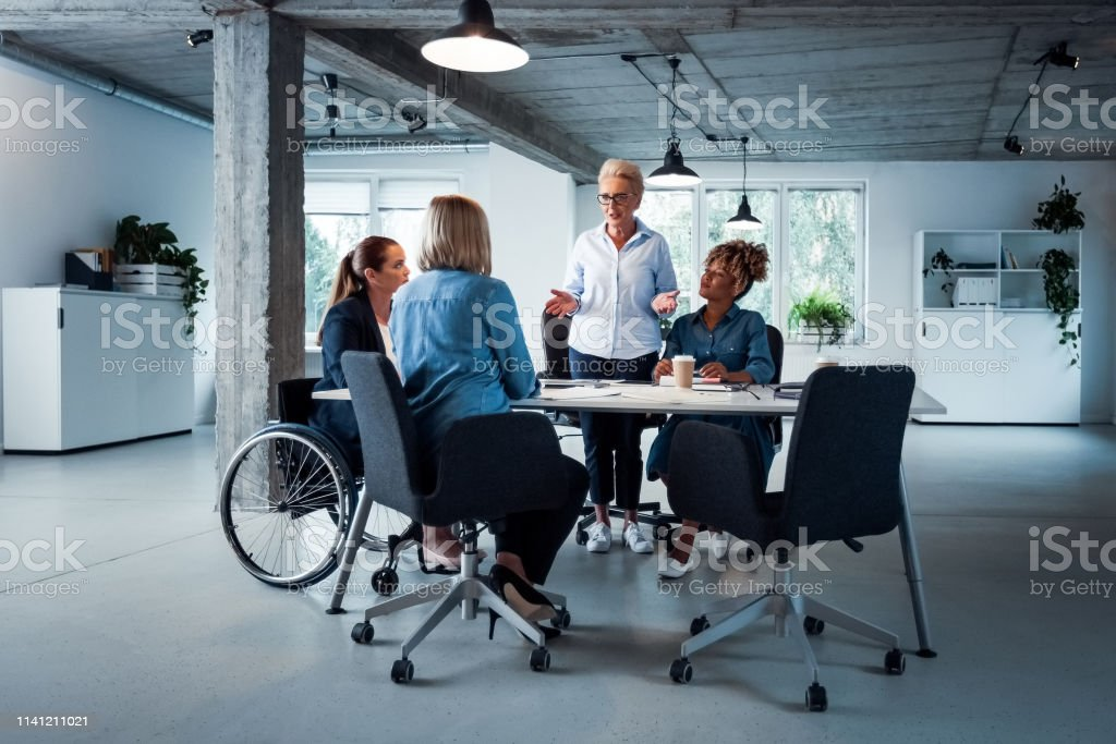 Senior businesswoman talking to executives at desk Senior businesswoman talking with female executives while standing at desk. Professionals are listening to their role model in office. They are working on start-up business. 35-39 Years Stock Photo