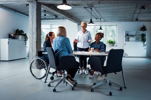 Senior Businesswoman Talking To Executives At Desk Stock Photo - Download Image Now