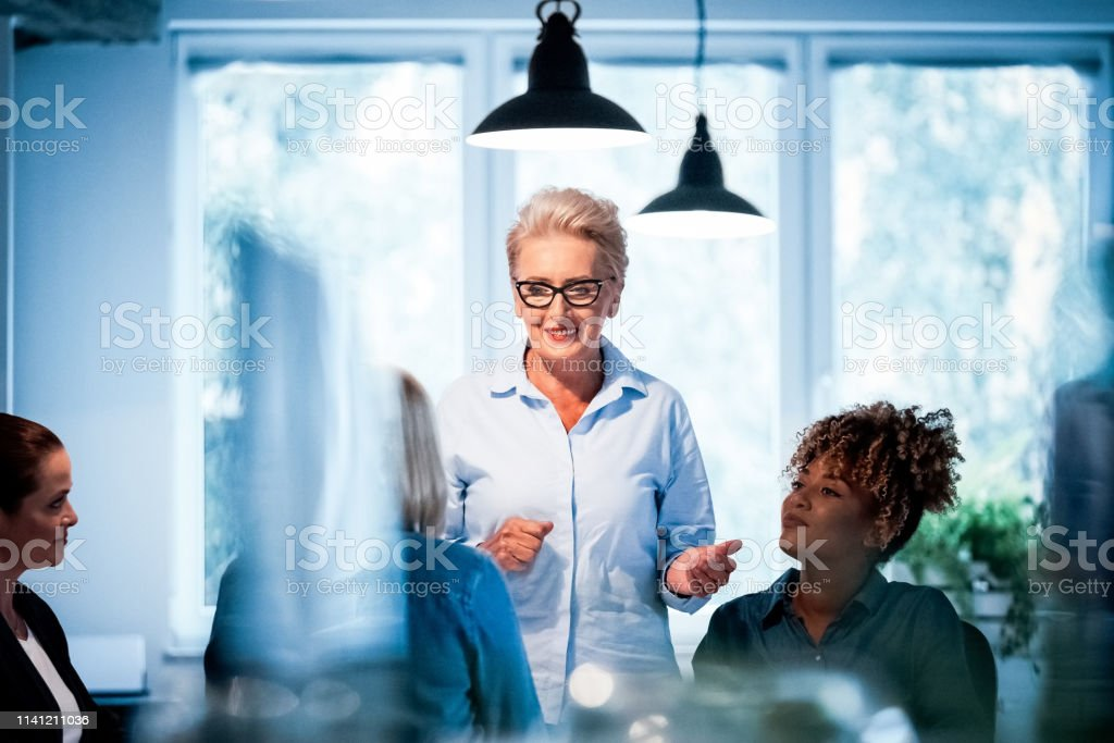 Senior businesswoman talking to female executives Senior businesswoman talking with female executives while standing. Professionals are listening to their role model in office. They are working on start-up business. 35-39 Years Stock Photo