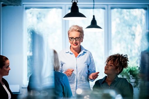 Senior Businesswoman Talking To Female Executives Stock Photo - Download Image Now