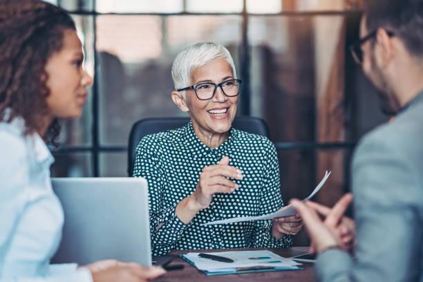 Senior businesswoman talking to her team stock photo