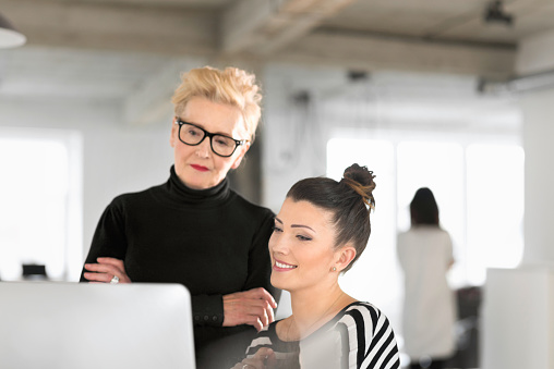 Senior Businesswoman Talking With Creative Young Woman In The Studio Stock Photo - Download Image Now