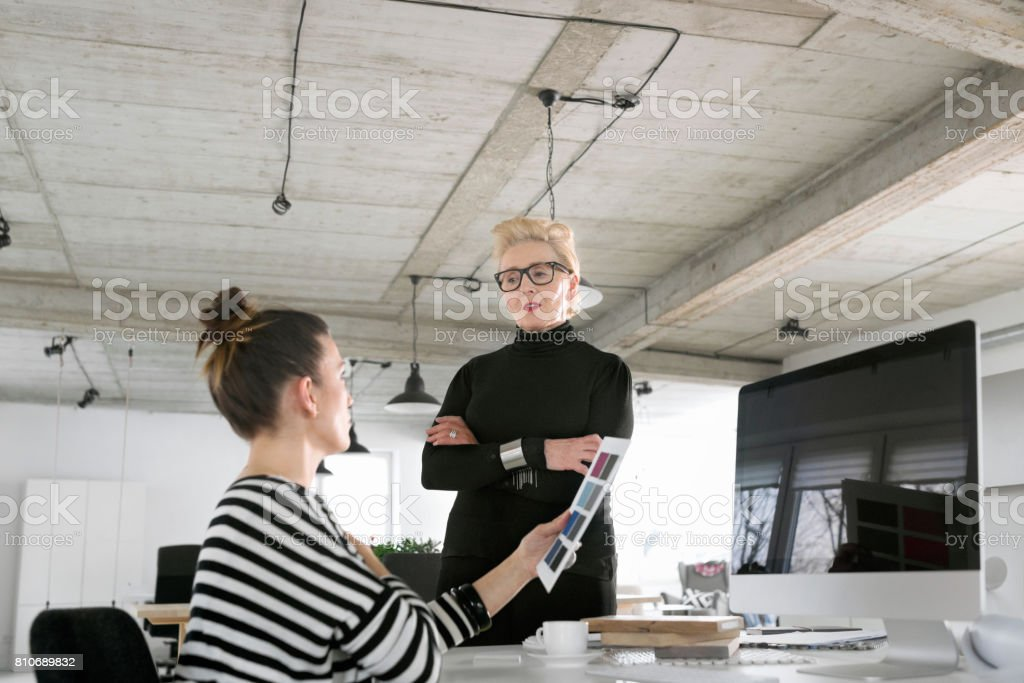 Senior businesswoman talking with creative young woman in the studio Senior businesswoman talking with creative young woman in the office, giving her an advice. 60-69 Years Stock Photo
