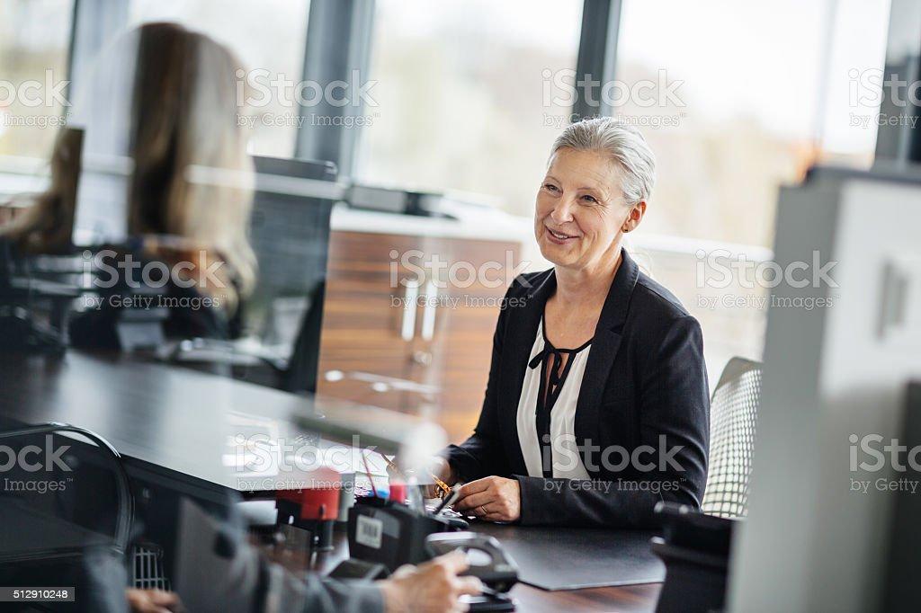 Senior Businesswoman talking with employee stock photo