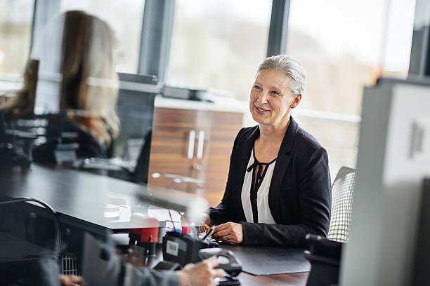 femme d'affaires senior avec l'employé - directrice photos et images de collection