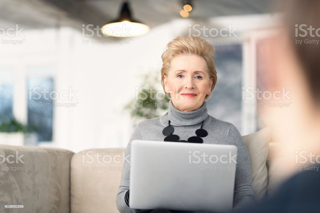 Senior businesswoman talking with young woman Senior woman talking with young businesswoman, giving advices, using laptop. 60-69 Years Stock Photo