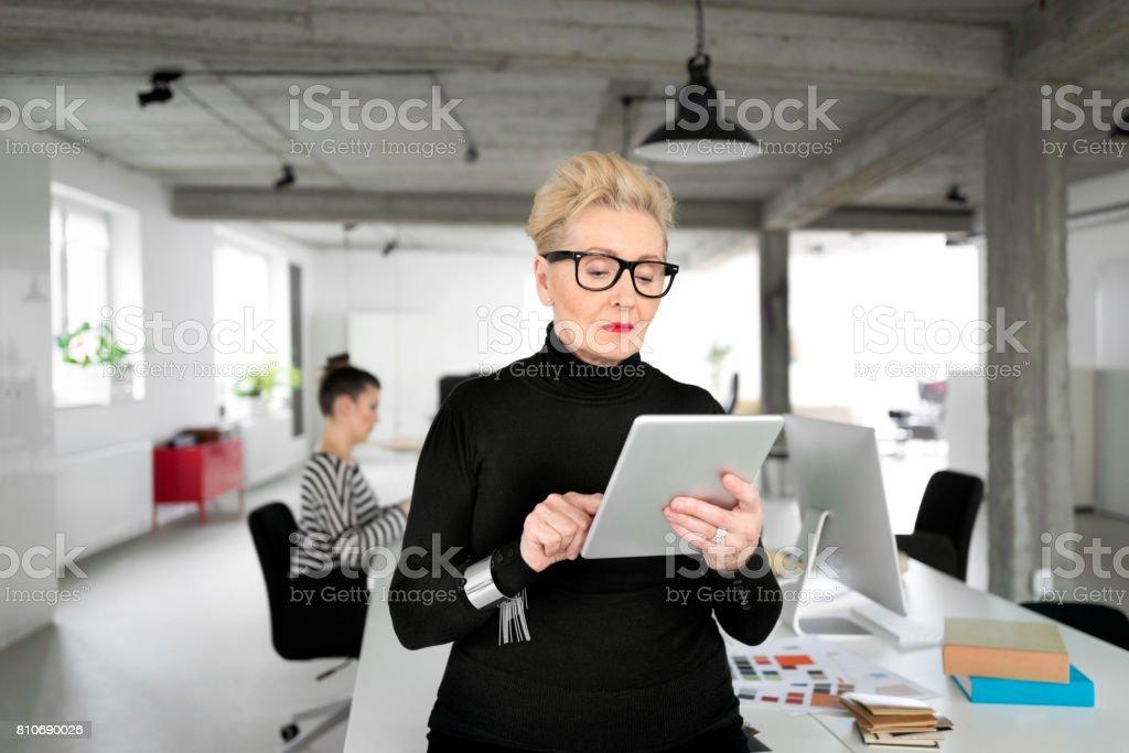 Senior businesswoman using a digital tablet in the office Portrait of senior elegant businesswoman using a digital tablet in her office. 60-69 Years Stock Photo