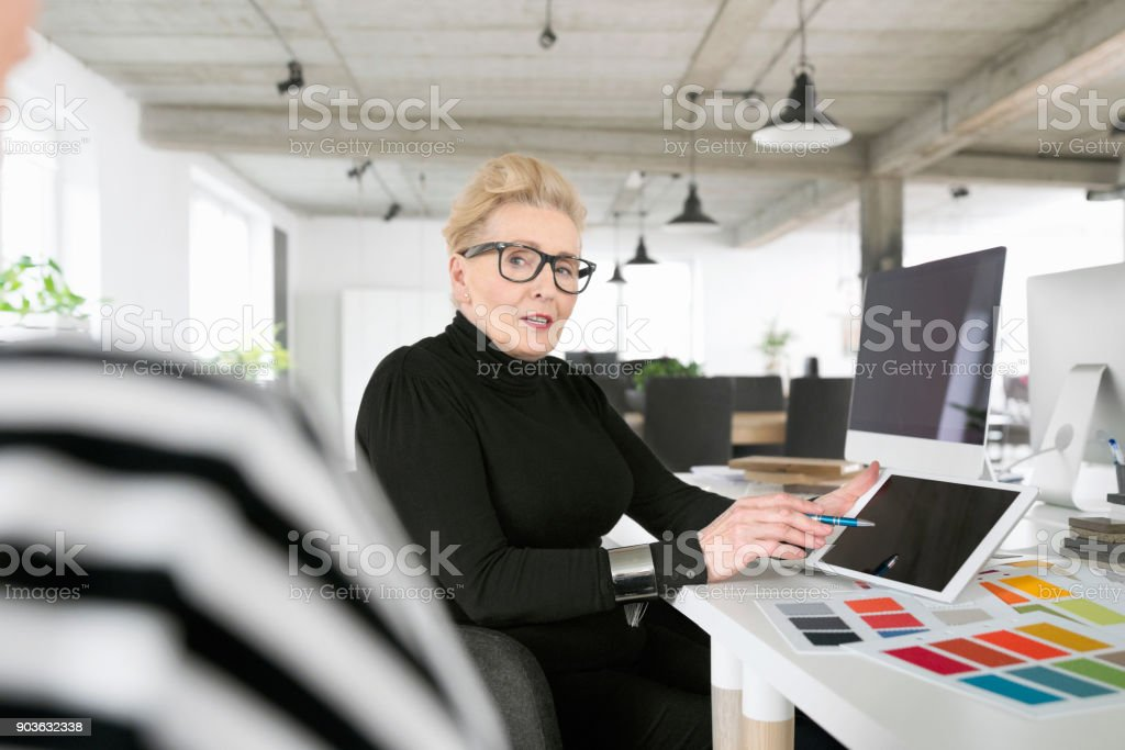 Senior businesswoman using a digital tablet in the office Senior interior designer sitting at the desk in the office, pointing at digital tablet and talking with her coworker. 60-69 Years Stock Photo