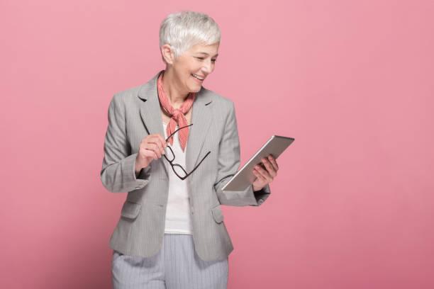 senior businesswoman using tablet - senior business woman tablet imagens e fotografias de stock