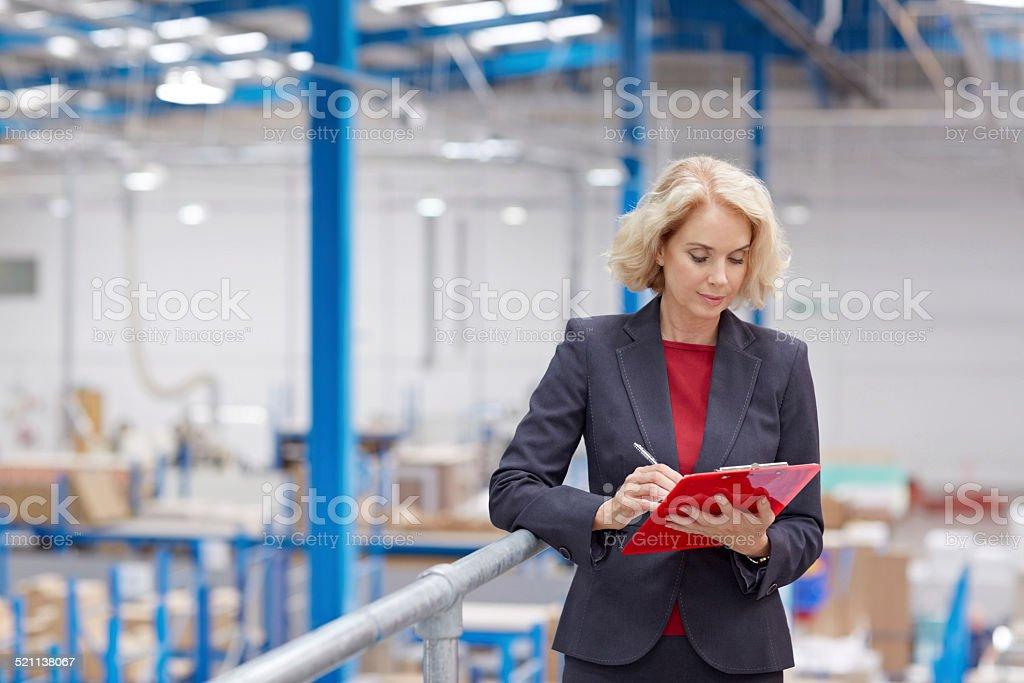Senior Geschäftsfrau mit Zwischenablage im warehouse – Foto