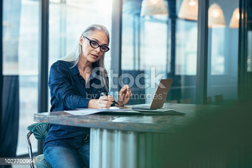 Portrait of senior woman sitting at table in office and reading few paper work. Business manager working on some documents at office.