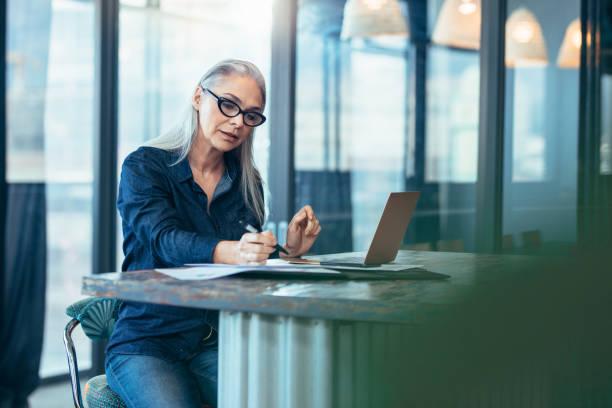 senior geschäftsfrau arbeiten im büro - schreibtischunterlagen stock-fotos und bilder