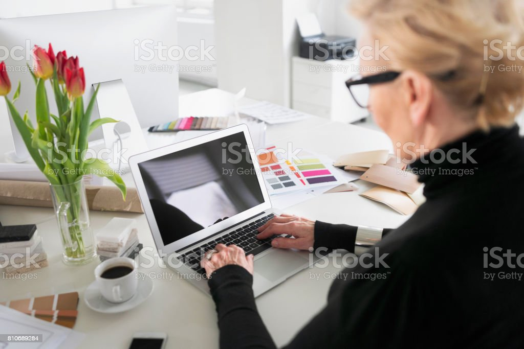 Senior businesswoman working on laptop in the office High angle view of senior businesswoman sitting at the desk in the office and using laptop. 60-69 Years Stock Photo