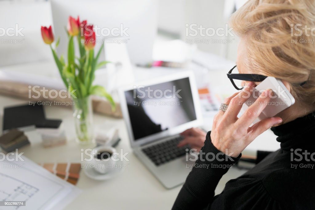 Senior businesswoman working on laptop in the office Senior businesswoman sitting at the desk in the office, using laptop and talking on phone. High angle view. 60-69 Years Stock Photo