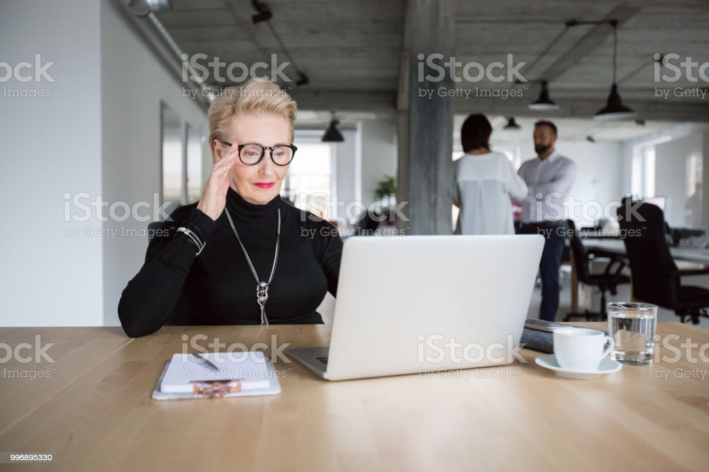 Senior businesswoman working on laptop Senior businesswoman sitting at a table and looking at laptop with coworkers talking in background Active Seniors Stock Photo