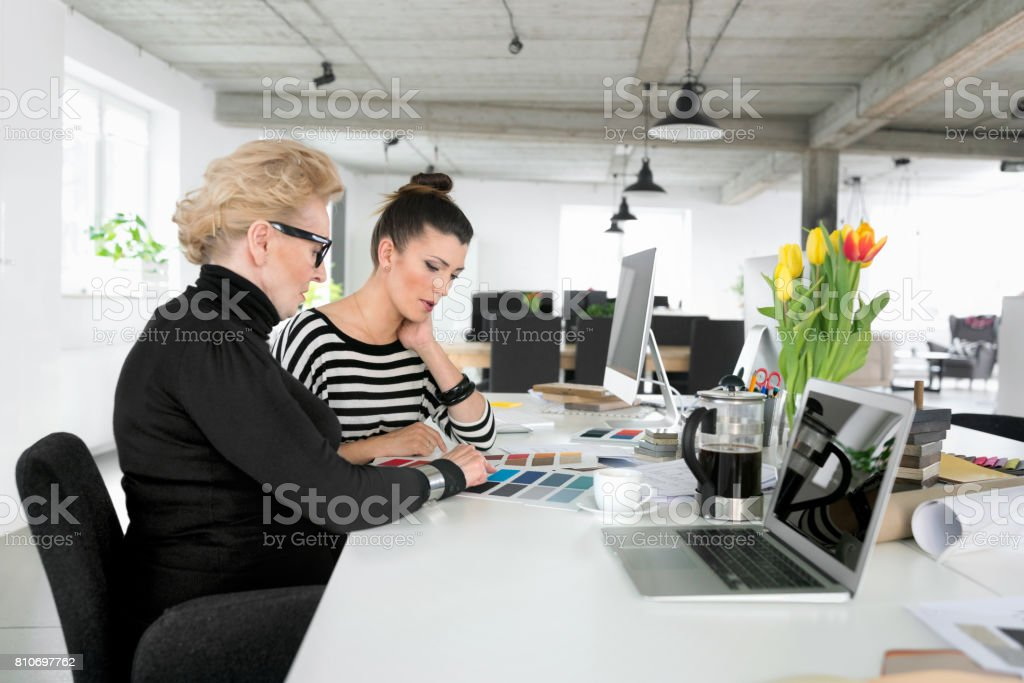 Senior businesswoman working together with young woman in the office Senior businesswoman working together with young woman in the office, looking at color samples. 60-69 Years Stock Photo