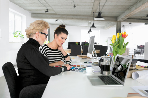 Senior Businesswoman Working Together With Young Woman In The Office Stock Photo - Download Image Now