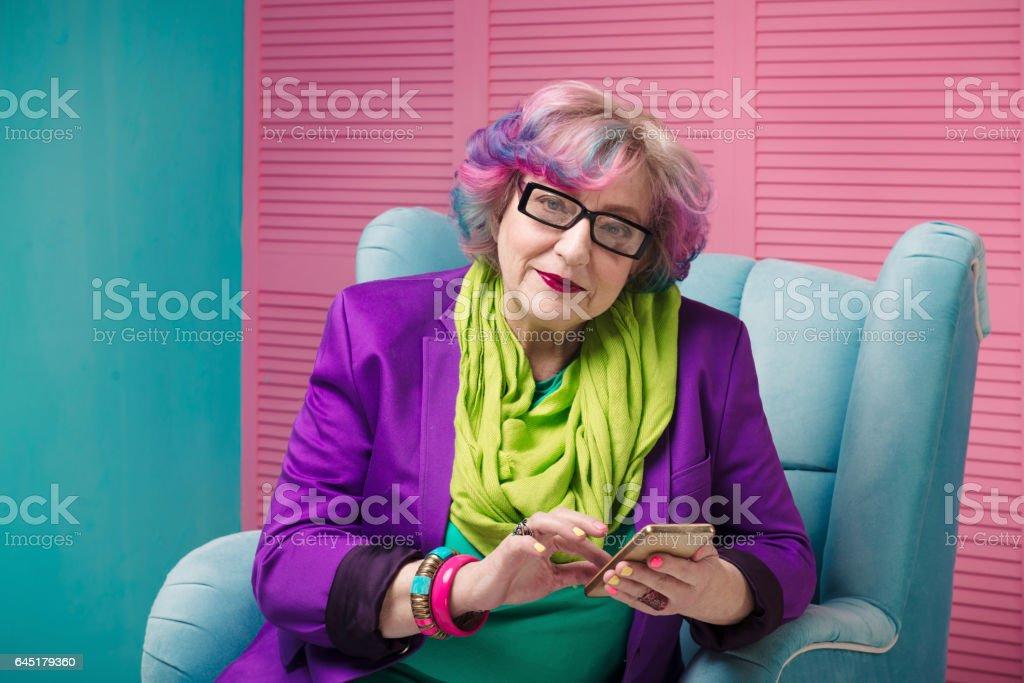 senior businesswomen holding golden phone in blue armchair, wearing glasses. - Photo