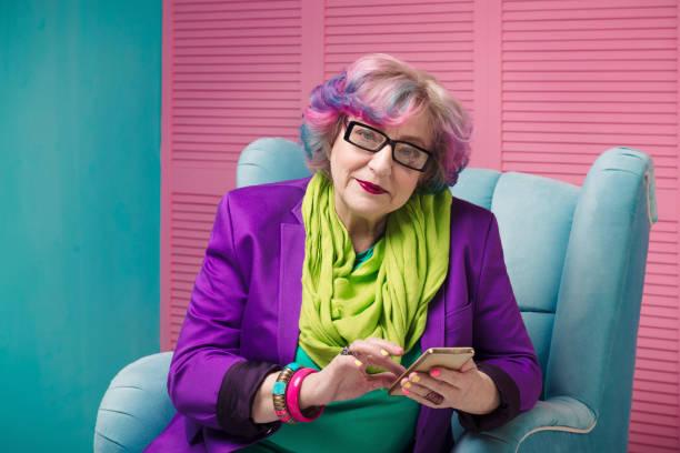 geschäftsfrauen, die goldenes telefon in blauem sessel halten, brille tragen. - flippige outfits stock-fotos und bilder