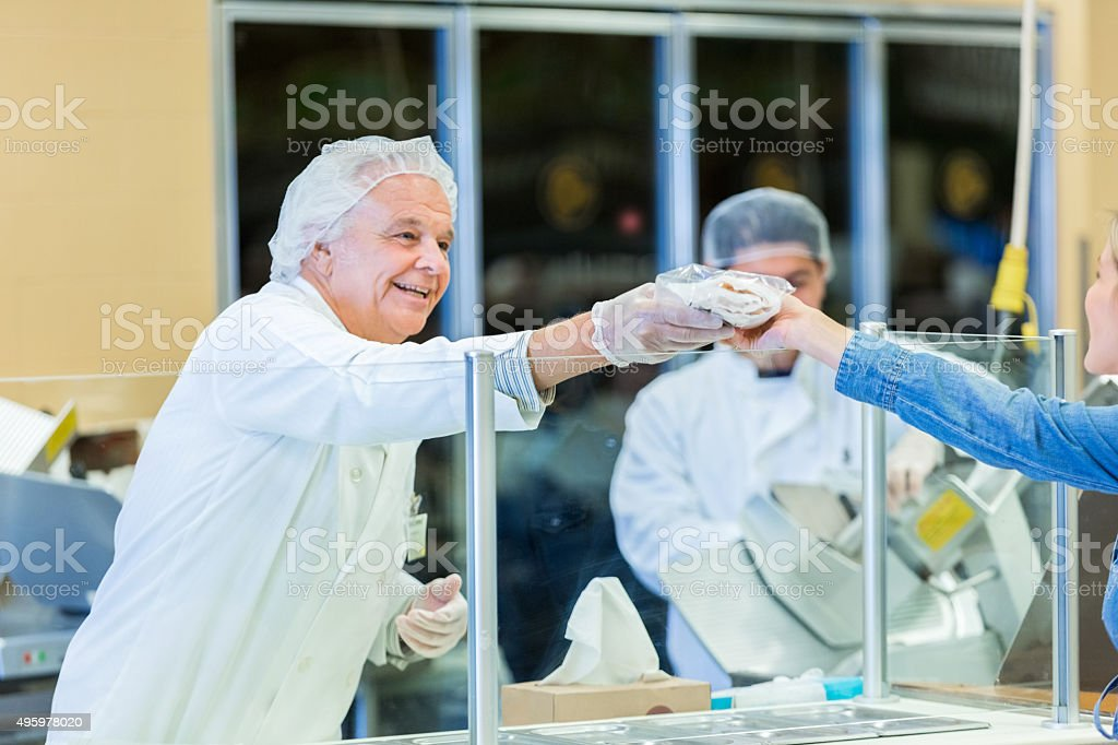 Senior butcher in grocery store handing product to customer stock photo