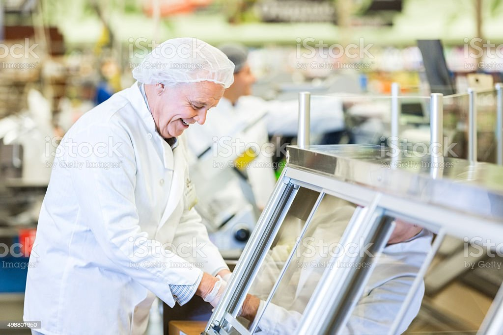 Senior butcher or deli employee packaging meat for customer stock photo