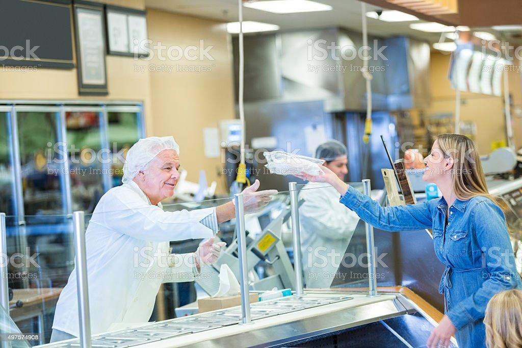Senior Fleischer oder Mitarbeiter helfen Kunden im Supermarkt – Foto