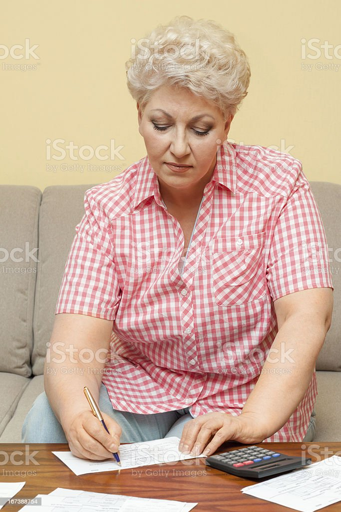 senior calculating her debts and write royalty-free stock photo