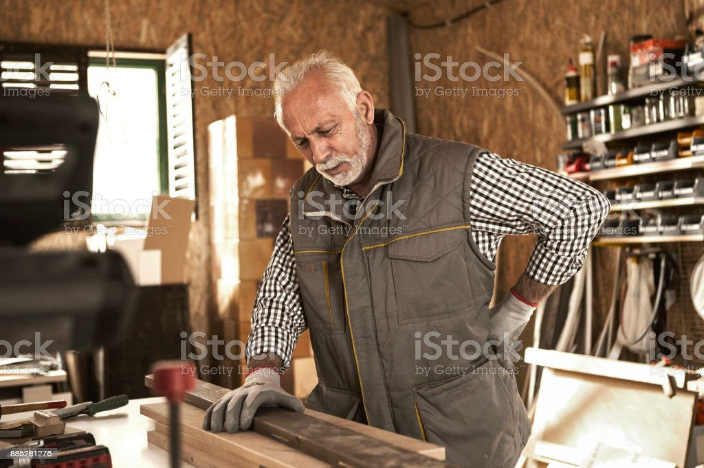 Senior carpenter having back pain Mature carpenter checking wood plank in his workshop 60-69 Years Stock Photo