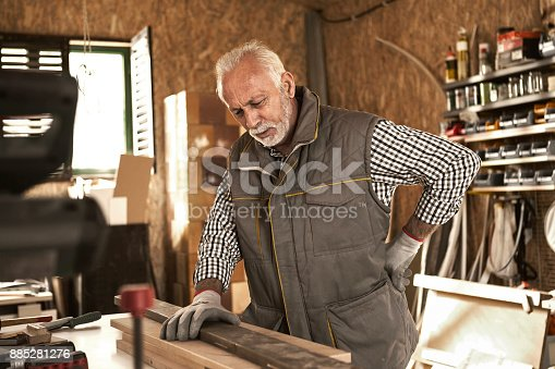 885281276istockphoto Senior carpenter having back pain 885281276