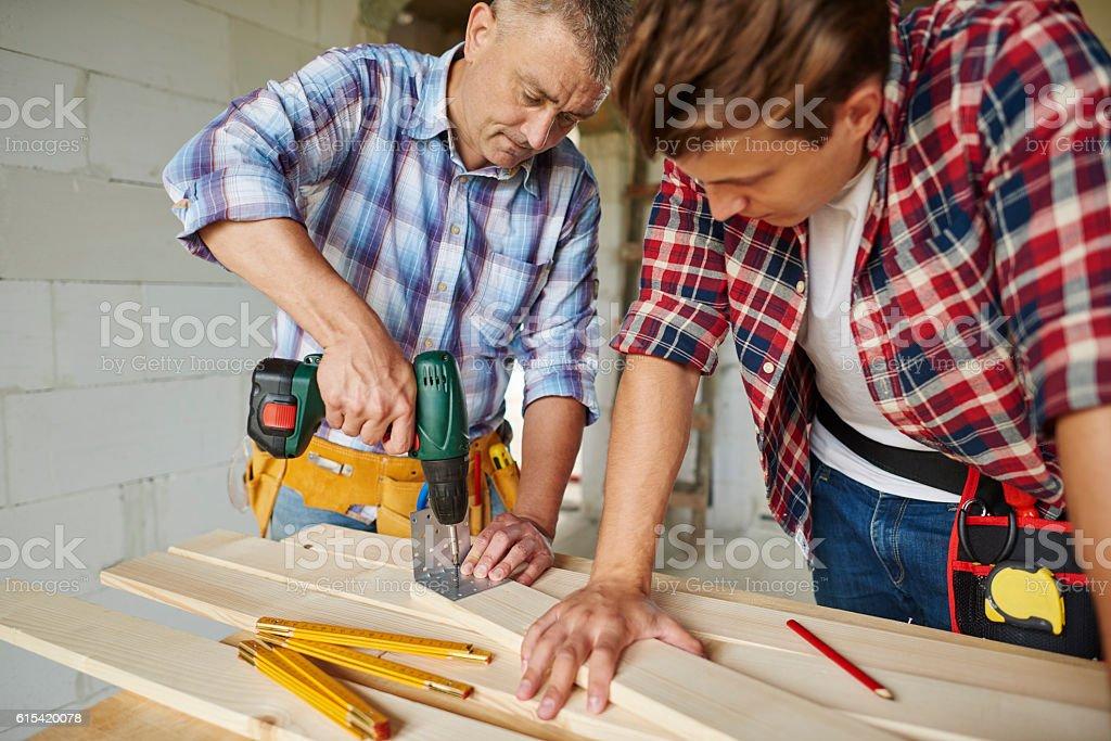 Senior carpenter is drilling  wooden planks stock photo