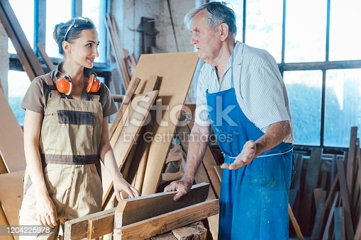 Senior carpenter sharing wisdom with younger aspiring woman colleague