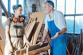 Senior carpenter sharing wisdom with younger aspiring woman colleague