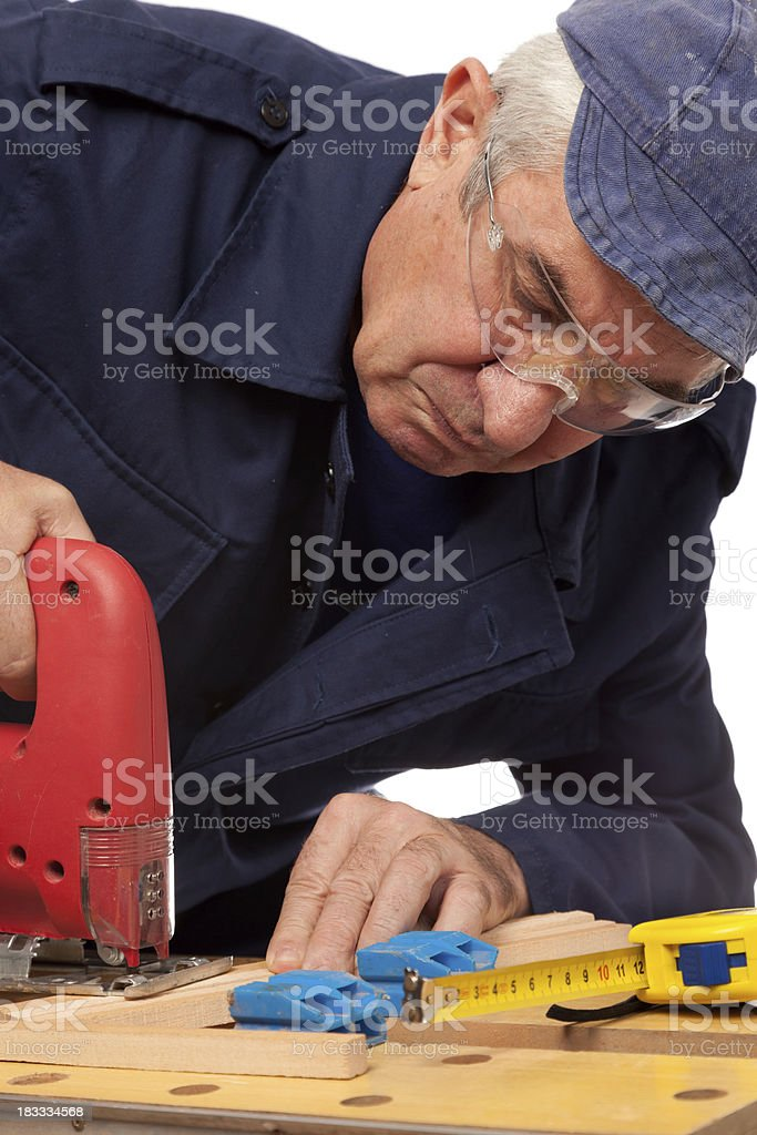 Senior carpenter using sawing equipment royalty-free stock photo