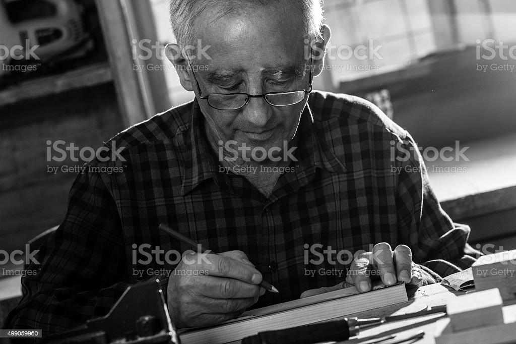 Senior carpenter workin in his workshop stock photo