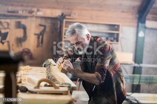 Senior Carpenter Working In His Old-Fashion Workshop