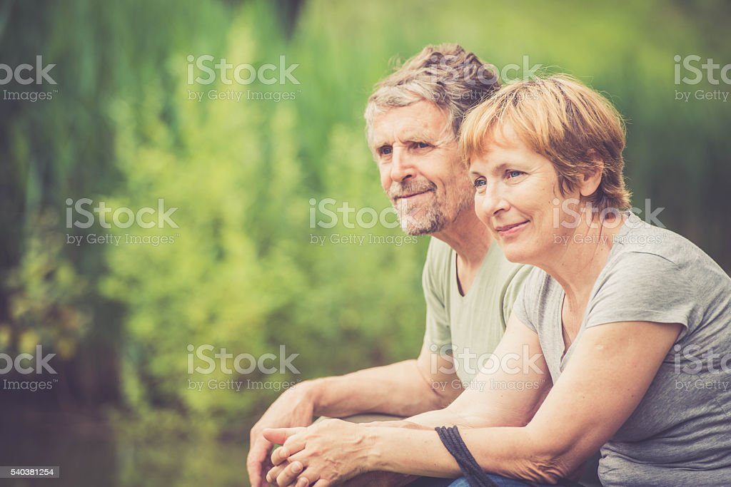 Senior caucasian couple outdoors portrait - looking around stock photo