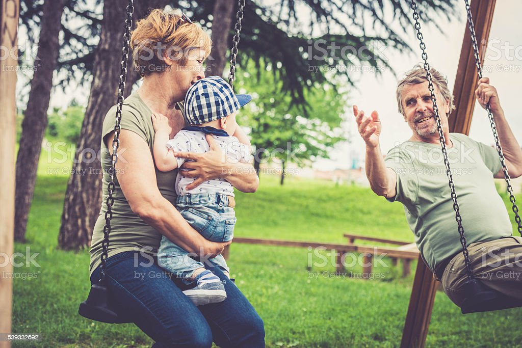 Senior caucasian couple outdoors with their grandson in city park stock photo