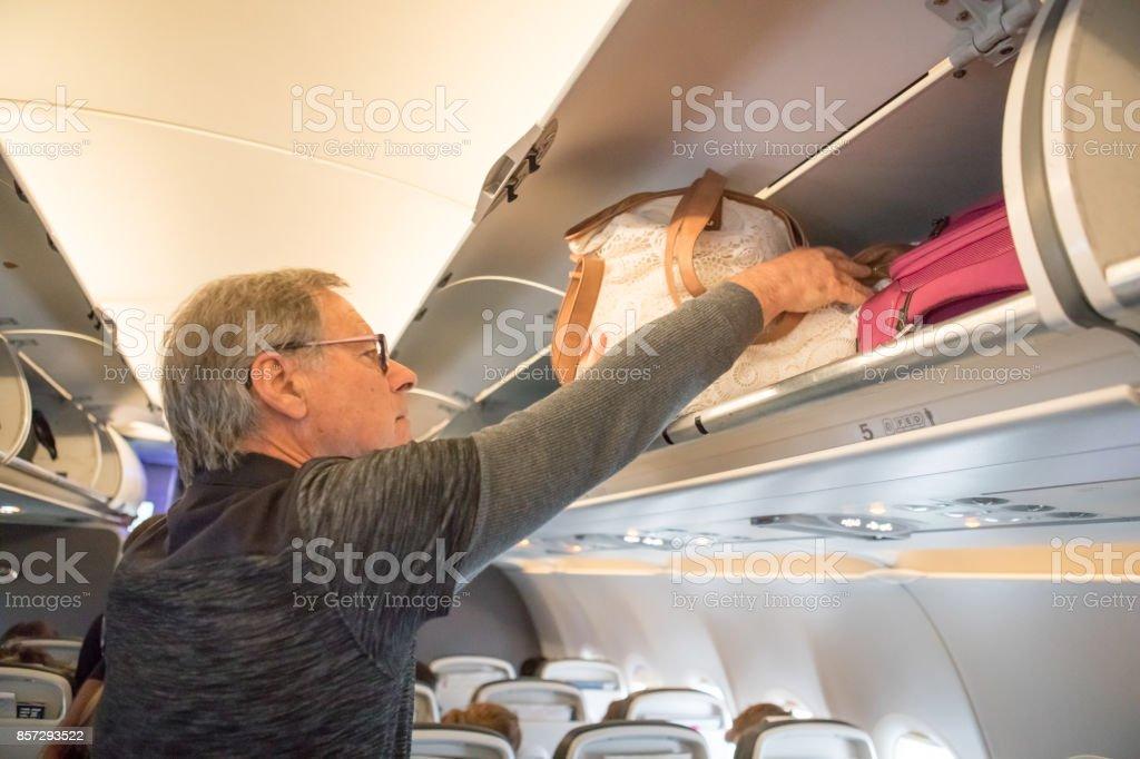 Senior caucasian male traveling on airplane stock photo