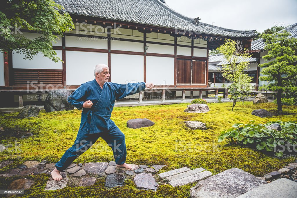 Senior Caucasian Man Exercising Karate in Buddhist Temple, Kyoto, Japan royalty-free stock photo